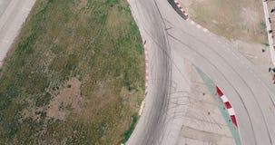 Powietrzny materia? filmowy samochodowy bie?ny ?lad z k?ta mistrzostwem jedzie filmowy asfalt pal?c? spojrzenie opon chmurnego dn zbiory wideo