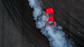 Powietrzny odgórnego widoku kierowcy dryfu fachowy samochód na asfaltu śladzie w fotografia royalty free