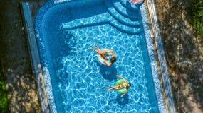 Powietrzny odgórny widok dzieci w pływackim basenie od above, szczęśliwi dzieciaki pływa na nadmuchiwanych ringowych donuts i zab Zdjęcia Stock