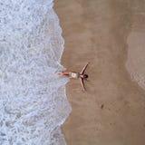 Powietrzny odgórny widok kobieta z jej rękami szeroko rozpościerać kłaść na piaskowatej plaży obrazy stock
