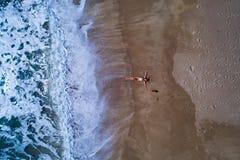 Powietrzny odgórny widok kobieta z jej rękami szeroko rozpościerać kłaść na piaskowatej plaży zdjęcie royalty free