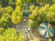 Powietrzny odgórny widok miasto parka caorusel z szczęśliwymi dziećmi na wakacjach letnich f zdjęcie stock