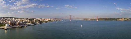 Powietrzny panoramiczny widok miasto Lisbon z żagiel łodziami na Tagus rzece i 25 Kwietnia most Ponte 25 De Abril na t Zdjęcie Royalty Free
