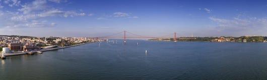 Powietrzny panoramiczny widok miasto Lisbon z żagiel łodziami na Tagus rzece i 25 Kwietnia most Ponte 25 De Abril na t Obraz Stock