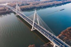 Powietrzny piękny strzał zawieszenie most nad wielką rzeką z łódkowatym żeglowaniem w nim zdjęcia stock