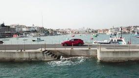 Powietrzny truteń lata wokoło samochodu który stoi na molu z jachtami zdjęcie wideo