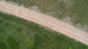 Powietrzny trutnia materiał filmowy Odgórny widok zlotny samochód na pył drodze zdjęcie wideo