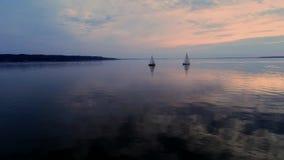 Powietrzny trutnia materiał filmowy pokojowa scena z jachtami pływa statkiem przy spokój wodą przy półmrokiem zdjęcie wideo