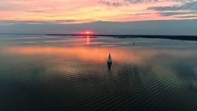 Powietrzny trutnia materiał filmowy pokojowa scena z jachtem pływa statkiem przy spokój wodą przy półmrokiem zbiory