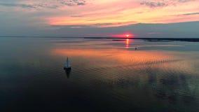 Powietrzny trutnia materiał filmowy pokojowa scena z jachtem pływa statkiem przy spokój wodą przy półmrokiem zbiory wideo