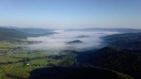 Powietrzny trutnia materiału filmowego widok: Lot nad jesieni górską wioską z lasami, polami i rzeką w wschodu słońca miękkim świ zbiory wideo