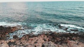 Powietrzny trutnia widok duże ocean fale uderza skalistą plażę i tworzy biel pianę zbiory wideo