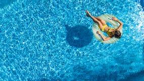 Powietrzny trutnia widok mała dziewczynka w basenie z góry, dzieciak pływa na nadmuchiwanym ringowym pączku, dziecko zabawę w błę fotografia stock