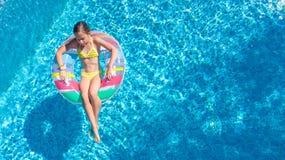 Powietrzny trutnia widok mała dziewczynka w basenie z góry, dzieciak pływa na nadmuchiwanym ringowym pączku, dziecko zabawę w błę zdjęcia royalty free