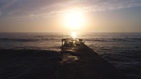 Powietrzny trutnia widok piękny wschód słońca nad morze fala starym łamającym mostem i zbiory