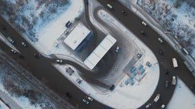 Powietrzny wirowy widoku ruch drogowy na okrąg drodze z benzynową stacją w zimy mieście zbiory wideo