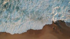 Powietrzny zasięrzutny szorstki biel macha rozbijać na skałach na plaży zbiory