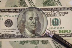 Powiększać - szkło kłama na sto dolarowych rachunkach Obraz Stock