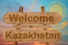 Powitanie Kazachstan znak na drewnianym tle z kontaminaci flaga państowowa Zdjęcia Stock