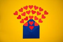 Powitanie koperta z papierowymi sercami na żółtym tle Serca nalewają z koperty Serca latają out od koperty Miłość Zdjęcia Stock