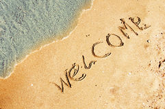 Powitanie pisać w piaskowatej plaży Zdjęcie Stock