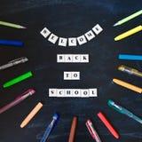 Powitanie z powrotem szkoły literowanie na blackboard Popiera szkoły inskrypcja na chalkboard Wiadomość na chalkboard Odgórny wid obraz stock