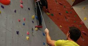 Powozowy pomagający kobiety w wspinać się sztuczną ścianę 4k zdjęcie wideo