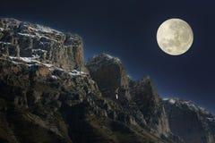 Powstający księżyc w pełni nad skalistymi szczytami Obrazy Stock