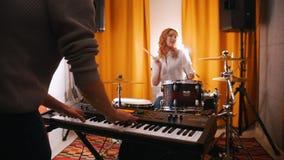 powtórka Facet bawić się na klawiaturach, dziewczyna dobosz przy backgrond Backlights Ostrość na rękach Widok od plecy facet zbiory