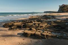 Powulkaniczne skały na piaskowatej plaży Zdjęcie Royalty Free