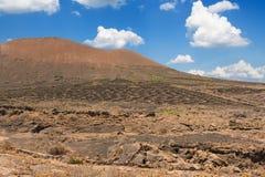 Powulkaniczny krater w Timanfaya parku narodowym pod niebieskim niebem z chmurami Lanzarote, Wyspa Kanaryjska, Hiszpania obraz royalty free