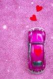 Pozafioletowy zabawkarski samochód niesie miłości czerwonego serce na dachu Poślubiać lub walentynki zaproszenia pocztówkowy poję Obraz Stock
