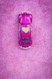 Pozafioletowy zabawkarski samochód niesie miłości zielonego serce na dachu Poślubiać lub walentynki zaproszenia pocztówkowy pojęc Fotografia Royalty Free