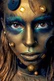 Pozaziemski niezwykły makeup z dekoracyjnymi elementami na twarzy, złota skóra Zdjęcia Royalty Free