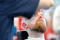 POZNAŃSKI, POLSKA, MAJ - 07 2016: Fryzjera męskiego golenia włosy żyletką przy T Obrazy Royalty Free