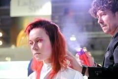 POZNAN - 18-ОЕ АПРЕЛЯ: Парикмахер аранжируя hairdo используя спрея для волос Стоковые Фото