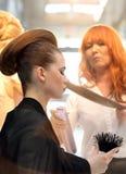 POZNAN - 18-ОЕ АПРЕЛЯ: Парикмахер аранжируя hairdo используя спрея для волос Стоковое Изображение