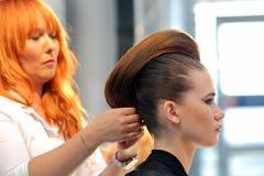 POZNAN - 18-ОЕ АПРЕЛЯ: Парикмахер аранжируя hairdo на щеголе взгляда Стоковое Изображение