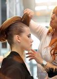 POZNAN - 18-ОЕ АПРЕЛЯ: Парикмахер аранжируя hairdo на щеголе взгляда Стоковое Фото