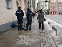 Police checking street musican. POZNAN - MARCH 16: Two police officers checking a street musician on March 16, 2013 in Poznan, Poland. Street musicians are stock photography