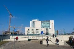 People by underground passage. Poznan, Poland - February 13, 2018: People walking by a underground passage with office building and crane in the background Royalty Free Stock Images