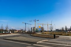 Road and constructions cranes. Poznan, Poland - February 13, 2018: Road with zebra crossing and construction cranes in the background Stock Photography