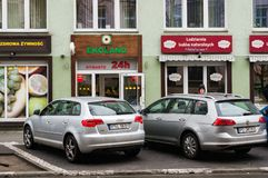 Ekoland 24h shop. Poznan, Poland - March 07, 2018: Audi and Volkswagen car parked in front of a Ekoland 24h shop and a natural ice cream bar royalty free stock image