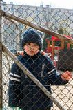 Boy and grid fence Stock Photo