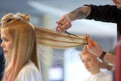 POZNAN POLEN - MAJ 07 2016: Frisör som klipper blont hår w Arkivbild
