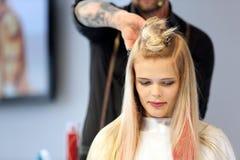 POZNAN POLEN - MAJ 07 2016: Frisör som klipper blont hår w Arkivbilder