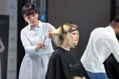 POZNAN POLEN - MAJ 07 2016: Frisör som klipper blont hår w Royaltyfri Fotografi