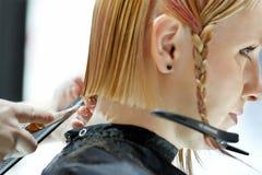 POZNAN POLEN - MAJ 07 2016: Frisör som klipper blont hår w Royaltyfria Bilder