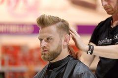 POZNAN POLEN - MAJ 07 2016: Frisör som ordnar frisyren på T Royaltyfri Fotografi