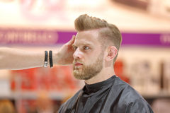 POZNAN POLEN - MAJ 07 2016: Frisör som ordnar frisyren på T Arkivfoto